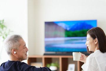 オリーブスマートイヤーでテレビを見ている夫婦