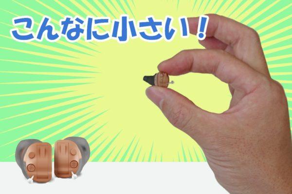 小さい耳あな型補聴器を持つ手